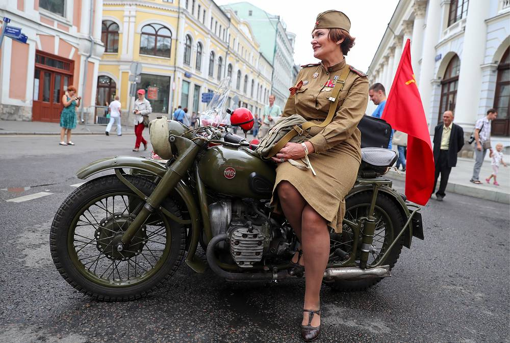 A woman dressed as WWII Red Army soldier sits on a Ural M-62 motorcycle