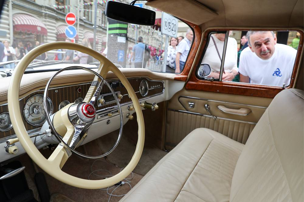 People examine the interior of a classic GAZ car