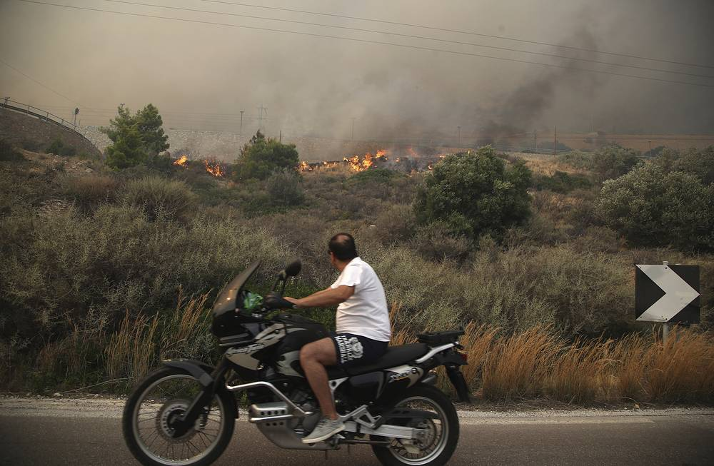 A motorcyclist looking at smoldering shrubbery on a road near Kineta, west of Athens