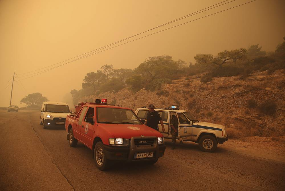 Members of the emergency services blocking a road near Kineta, west of Athens