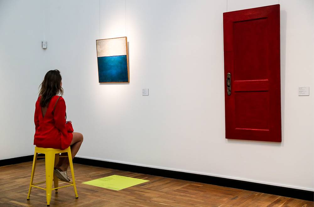 """A girl views Wall (1963) by Yevgeny Rukhin and Door (1965) by Mikhail Roginsky on display at the """"Tretyakov: Another Edition"""" experimental exhibition opened at Moscow's State Tretyakov Gallery, Moscow, July 25"""