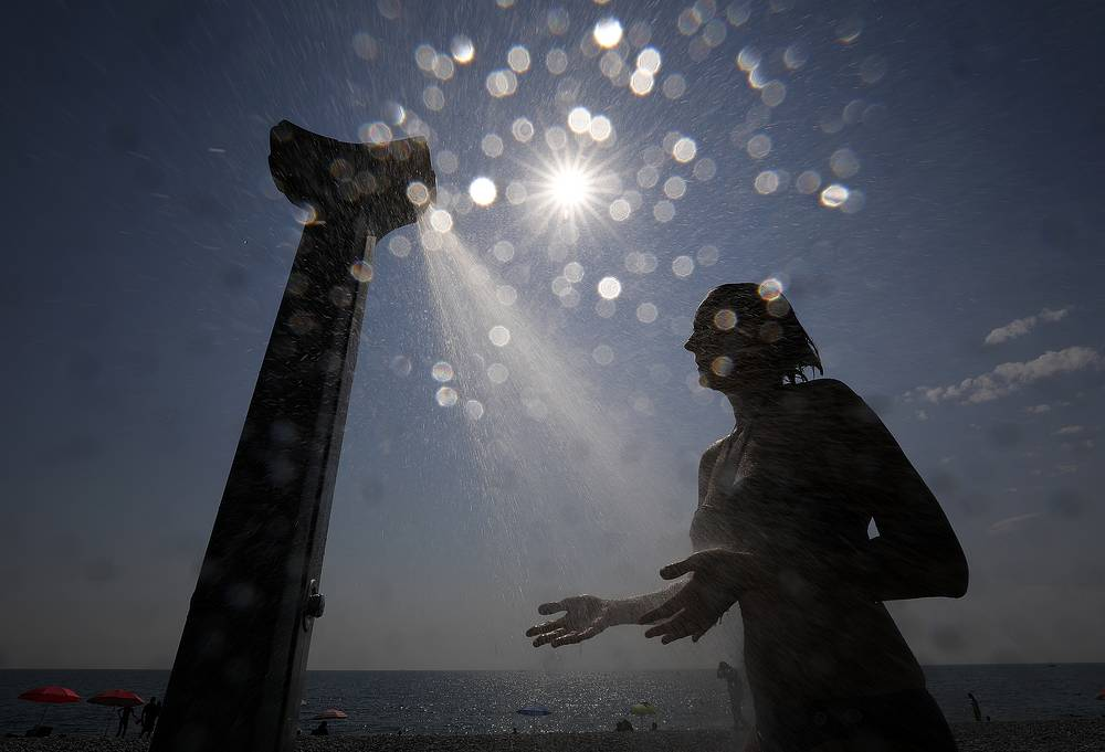 A woman takes a shower after swimming at the beach of Villeneuve-Loubet, France