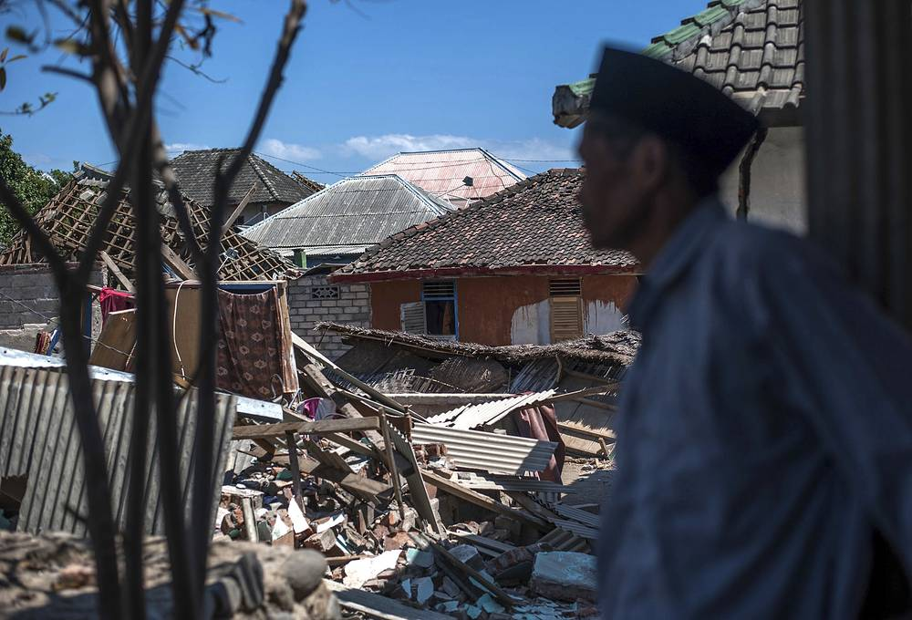 An Indonesian man inspects the damage in a village from a major earthquake in Kayangan on Lombok Island