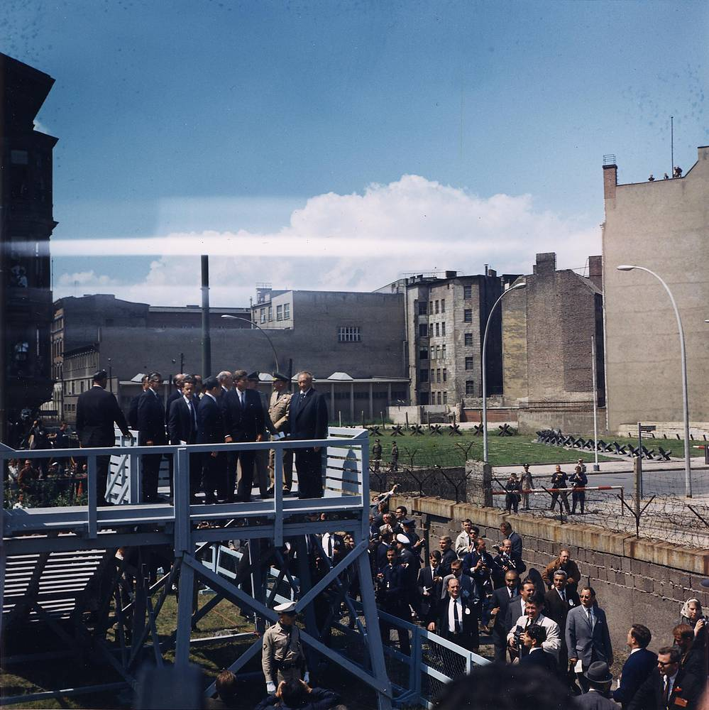 US President John F. Kennedy views East Berlin, East Germany, from an elevated platform at Checkpoint Charlie along the Berlin Wall in West Berlin, West Germany, June 26, 1963