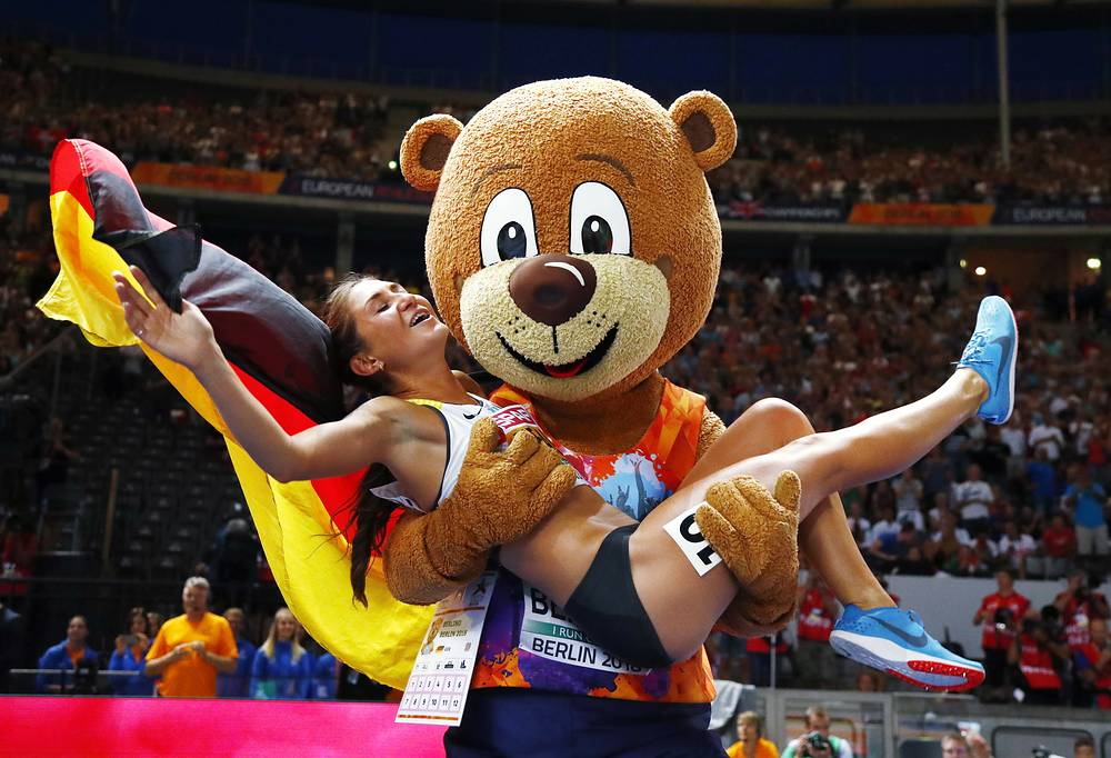 Germany's Gesa-Felicitas Krause is lifted by mascot Berlino as she celebrates after winning the gold medal in the women's 3000-meter steeplechase at the European Athletics Championships in the Olympic stadium in Berlin, August 12
