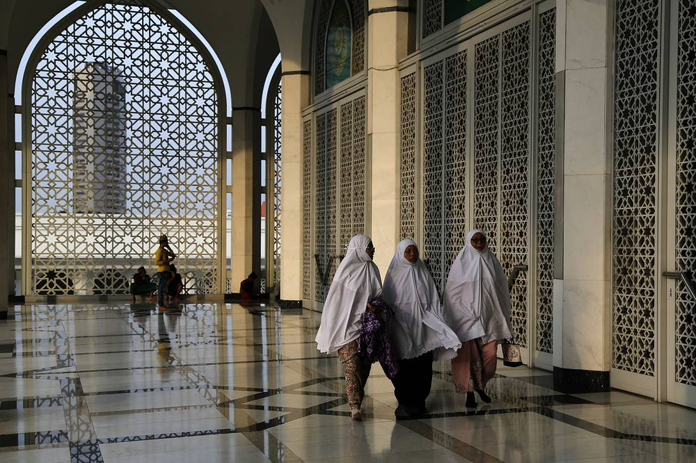 Malaysia Muslim women arrive for prayer during the Islamic holiday of Eid al-Adha at a mosque in Shah Alam, Malaysia
