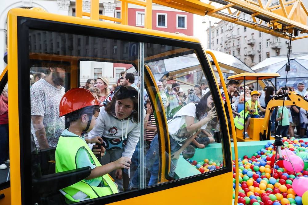 A boy operates a toy crane during Moscow City Day celebrations