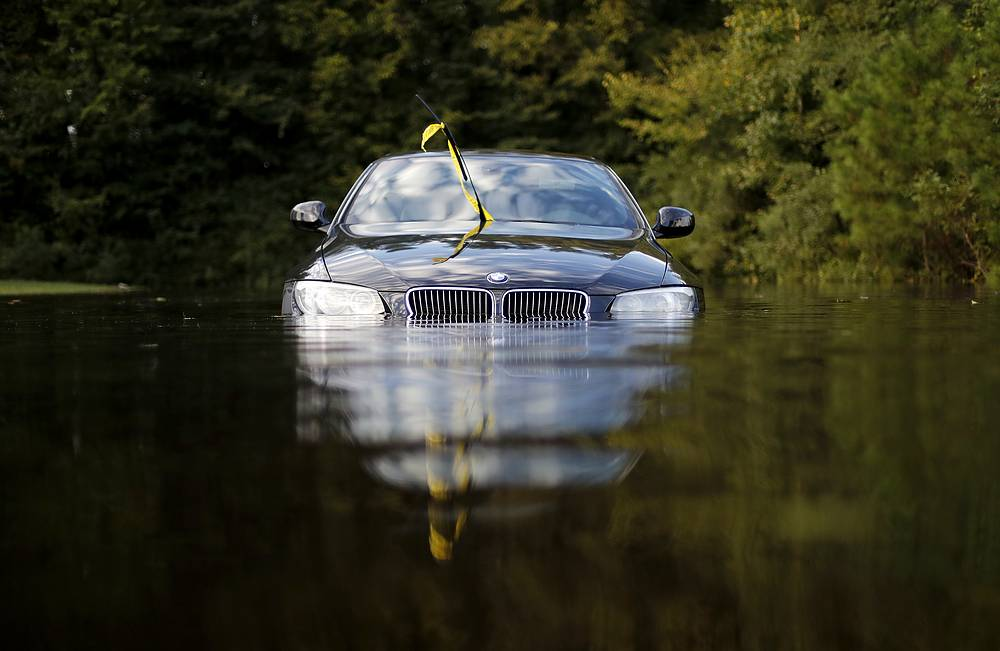 A car sits in a flooded parking lot at an apartment complex near the Cape Fear River in Fayetteville, North Carolina