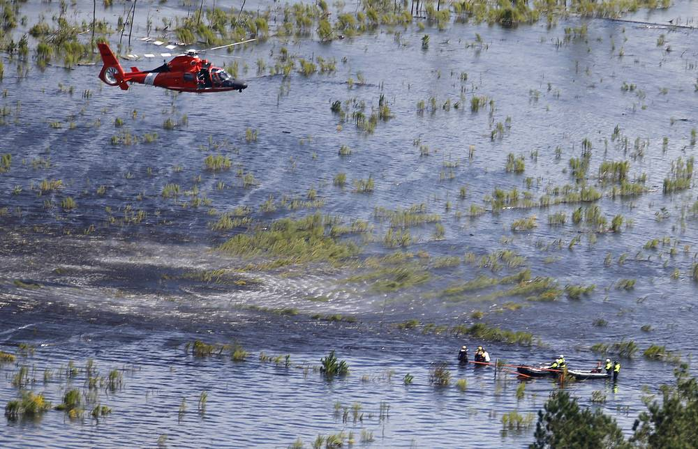 A US Coast Guard helicopter crew prepares to hoist a group of stranded residents from their flooded homes in Burgaw, North Carolina