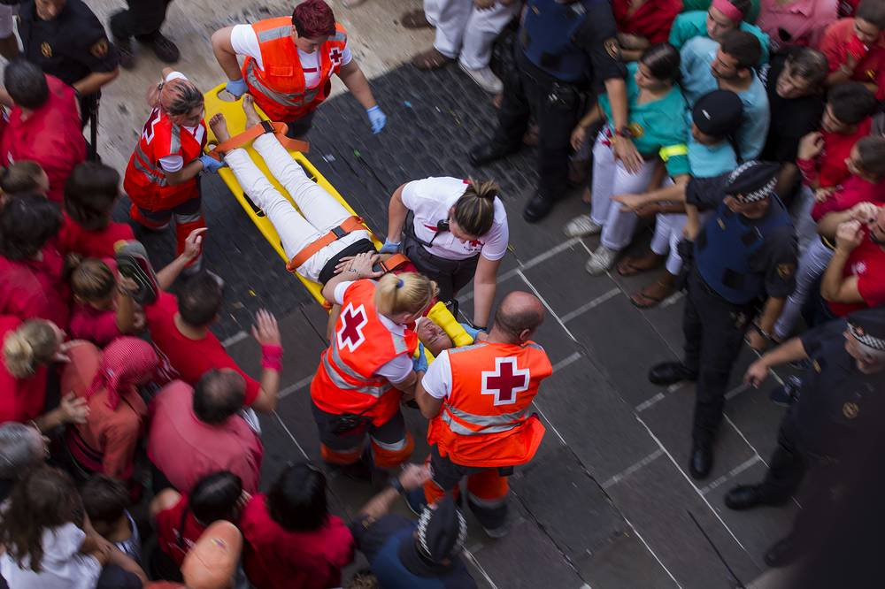 An injured member of a casteller is taken on stretcher by emergency services