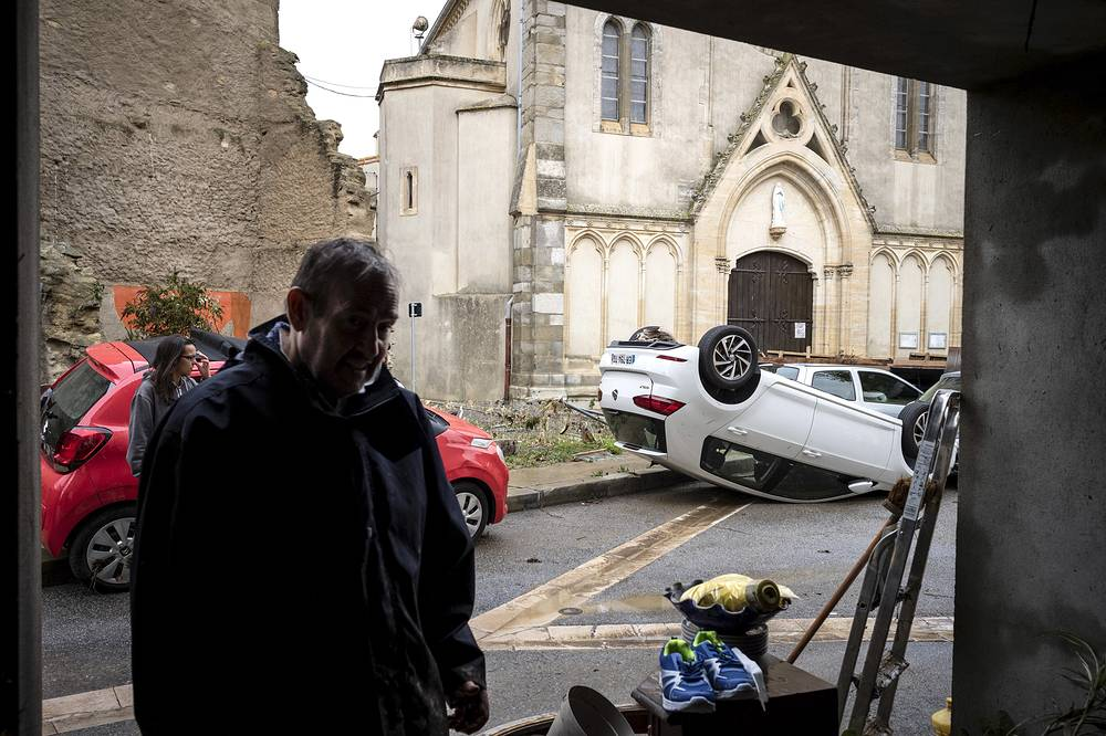 An overturned car is pictured in front of a church in the town of Villegailhenc, southern France