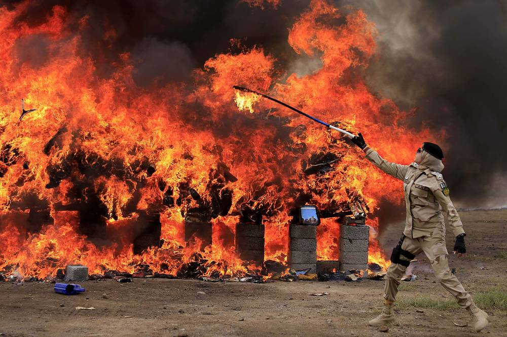A soldier from Pakistan Anti-Narcotics Force torches a pile of narcotics during a ceremony to burn piles of hashish, in Peshawar, October 16