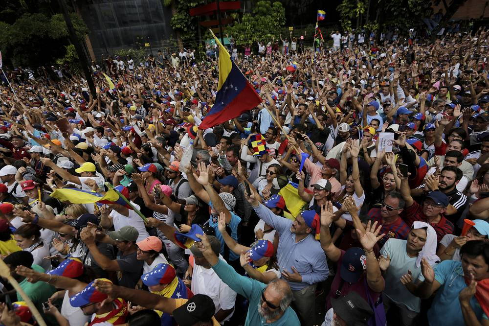 Anti-government protesters hold their hands up during the symbolic swearing-in of Juan Guaido in Caracas