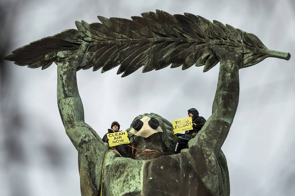 Environmental activists of Greenpeace demonstrate against the capital's air pollution on the statue of Freedom on top of Gellert Hill in Budapest, February 26