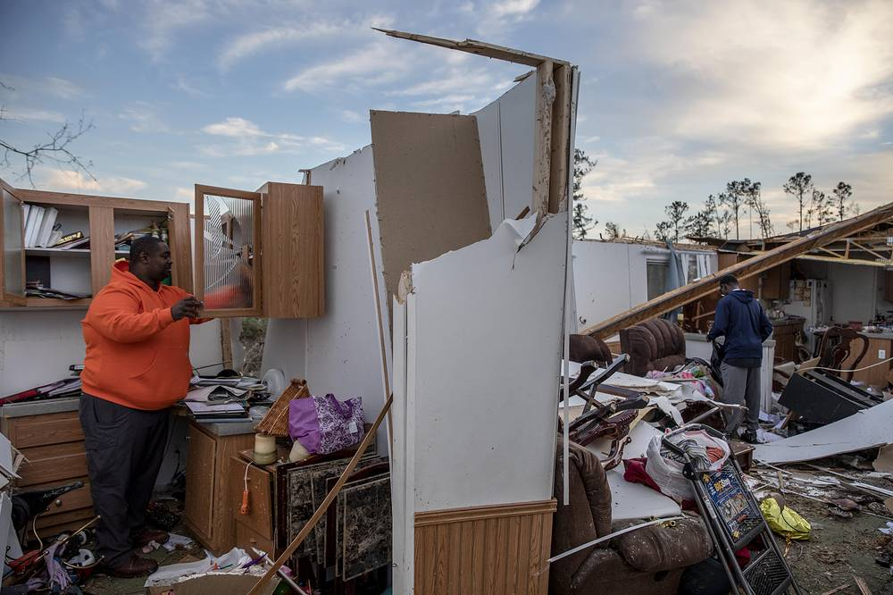 Local residents retrieve personal items from the damaged home where they survived a tornado a day earlier in Beauregard,  March 4