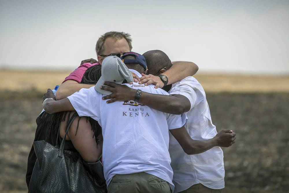 Family members and friends hug at the scene of the plane crash in Ethiopia