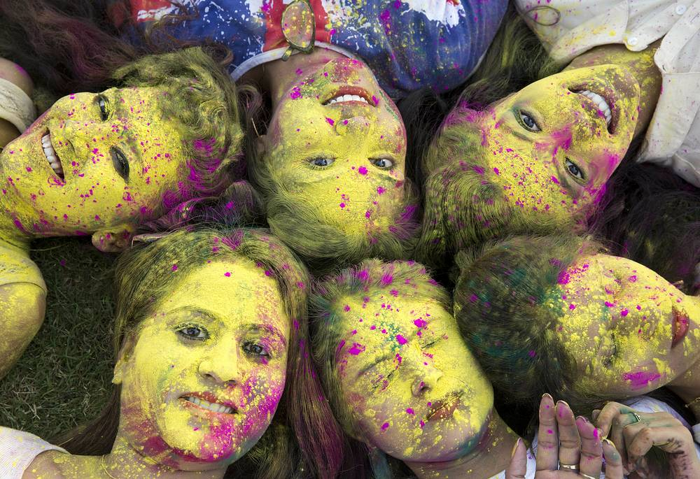 Indian girls pose for a photograph during Holi festival celebrations in Allahabad