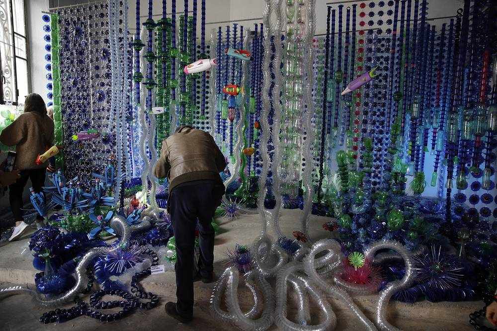 A man takes pictures of an installation by designer Arsenio Rodriguez, made with 20.000 recycled plastic bottles, displayed at the 'RO Plastic exhibition', part of the Salone del Mobile Furniture Fair week