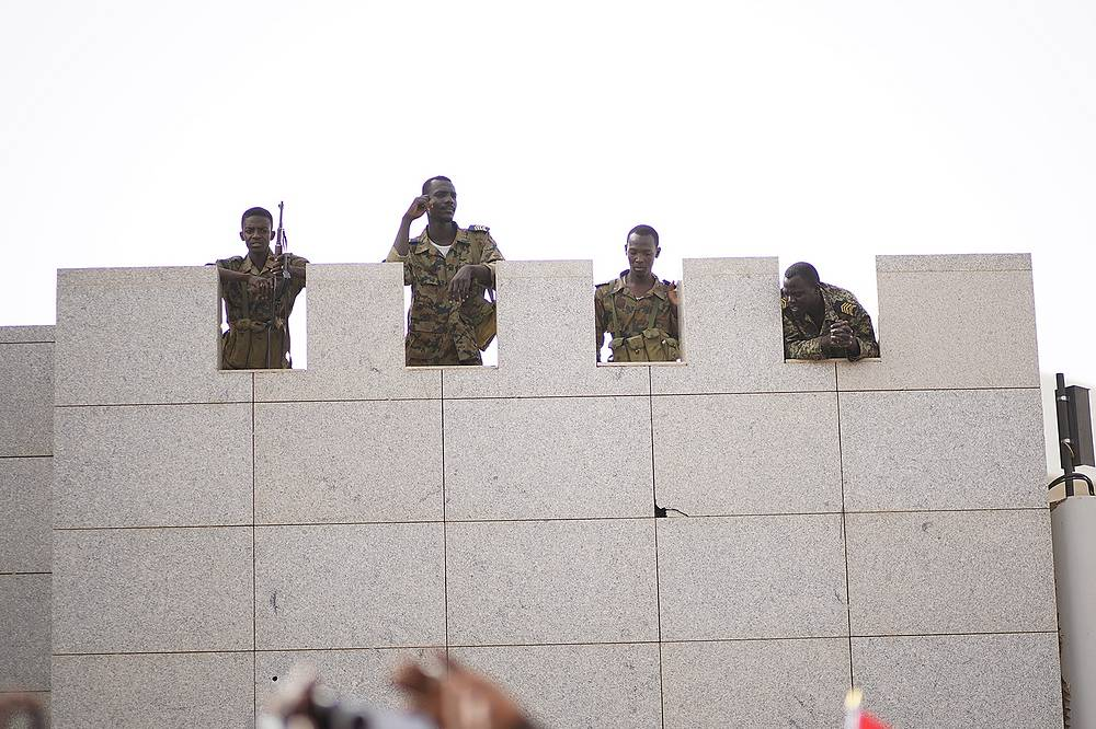 Soldier looking down on protesters demanding the departure of Sudanese President Omar al-Bashir outside the Sudanese Army headquarters in Khartoum