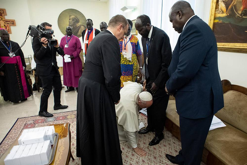 Pope Francis bends to kiss the feet of the South Sudan President President Salva Kiir Mayardit alongside other leaders gathered by him for the peace initiative, at the Vatican City, April 11