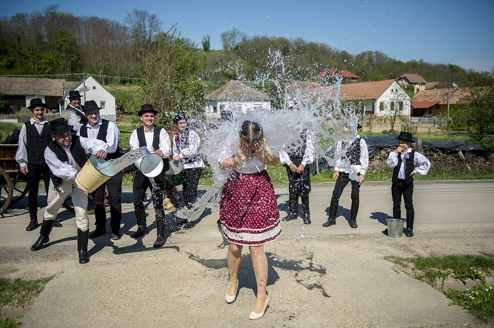 Young men pouring water on a women during traditional Easter sprinkling in Ciko, Hungary, April 22. According to a tradition of Hungarian villages, young men pour water on young women who in exchange present their sprinklers with beautifully colored eggs on Easter Monday