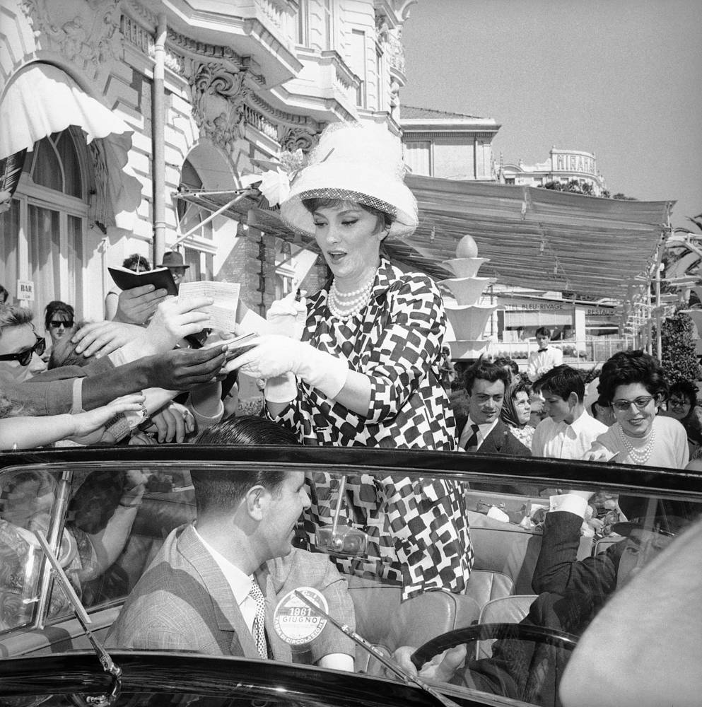 Italian actress Gina Lollobrigida standing in her open car giving out autographs to the crowd of fans standing in front of her hotel, in Cannes, 1961