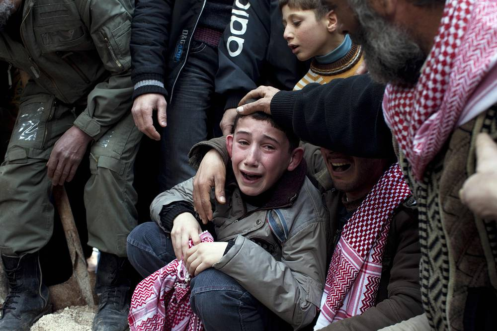 Ahmed, center, mourns his father Abdulaziz Abu Ahmed Khrer, who was killed by a Syrian Army sniper, during his funeral in Idlib, north Syria, Thursday, March 8, 2012. AP Photo/Rodrigo Abd