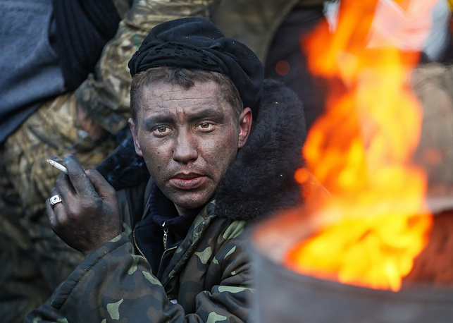 A protester smokes a cigarette near a metal barrel with fire. Barrel fires were the main way to warm yourself when temperatures in Kiev dropped to 20 degrees below zero in the end of January