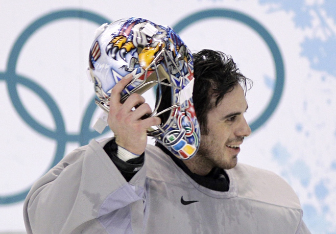 USA goalie Ryan Miller pulls on his helmet after a break during men's ice hockey practice at the Vancouver 2010 Olympics in Vancouver