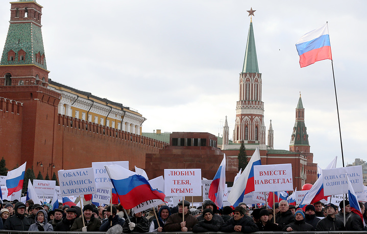 Russians hold banners reading 'Love you Crimea!' and 'Believe Putin!' during a rally celebrating the joining of Crimea and Sevastopol with Russia on Red Square in Moscow