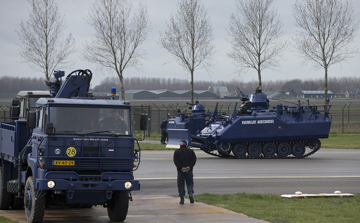 Dutch military police vehicles guard a section of Schiphol airport where China's President Xi Jinping is expected to arrive