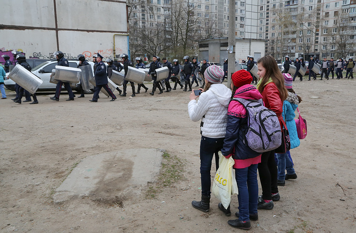 Schoolchildren watch policemen near of the district court in Kharkiv