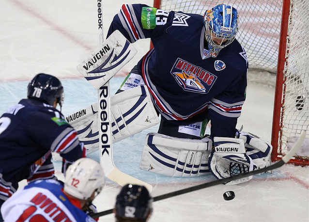 Metallurg's goalie Vasily Koshechkin (R) makes a save
