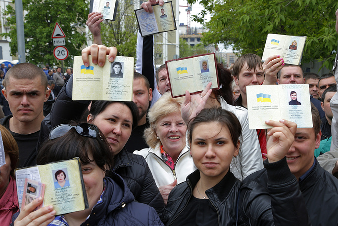 Ukrainians, who are in Russia at the moment, show off their passports while queuing to get their referendum ballot papers and vote, in Moscow