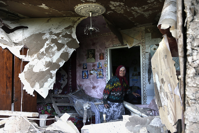 A woman looks at her house destroyed in a shelling attack in east Ukraine's Sloviansk
