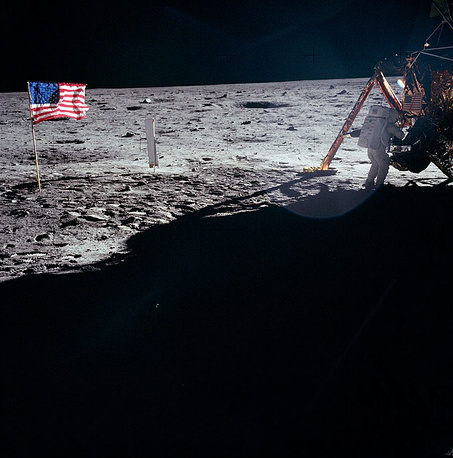 Neil Armstrong working at the base of the lunar module on the moon