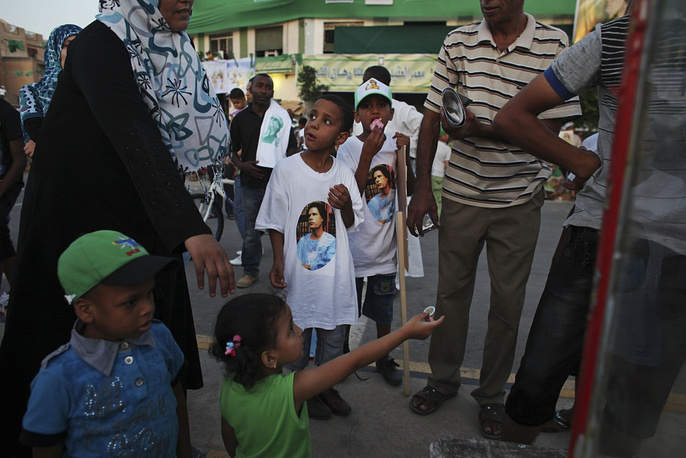 Children wearing T-shirts with the portrait of former Libyan leader Muammar Gaddafi
