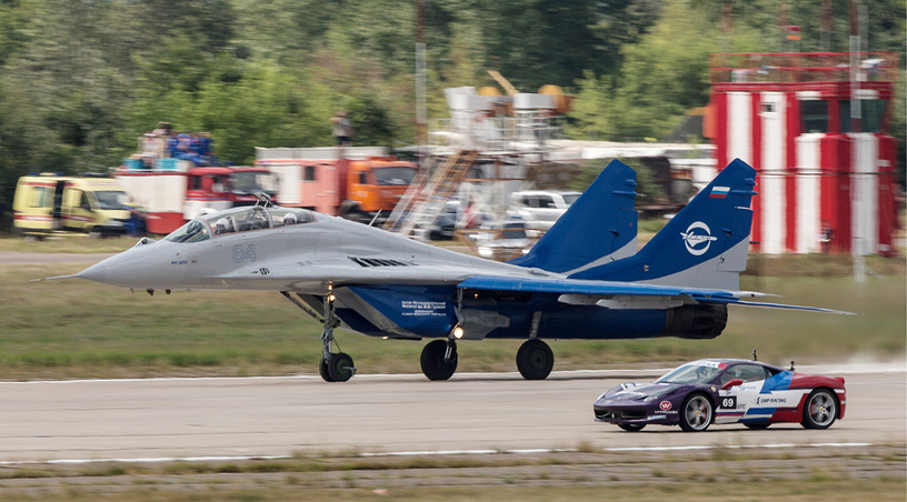 A MiG-29 jet fighter and a Ferrari 458 Italia compete during the Forsazh (Boost) car and air show