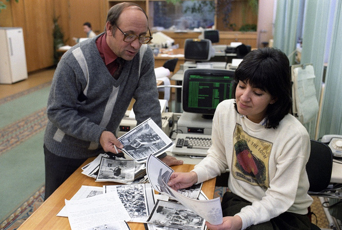 Executive editor in chief Konstantin Alexeyev and editor Yelena Nesterova are looking through images received by the real-time production desk of the TASS Graphic and Photo Information Editorial by means of facsimile, 1988
