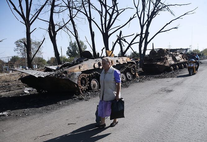 Around 366,900 Ukrainians have fled to neighboring countries, most of them to Russia. The number of internally displaced ammounts to 263,000. Photo: a local walks past Ukrainian armoured vehicles destroyed during the conflict
