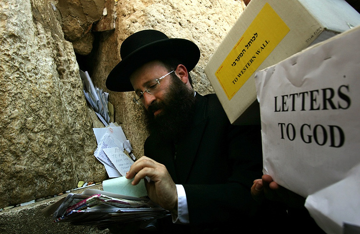 Thousands of letters addressed to God arrive to the Jerusalem main post office every year from all over the world and are collected and placed at the Judaism's holiest site. Photo: Letters written and addressed to God at the Western Wall in the old city of Jerusalem Wednesday, June 15, 2005