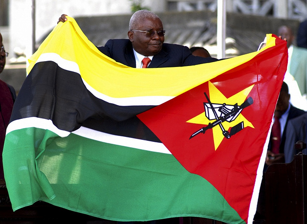 Photo: President of Mozambique Armando Guebuza with the national flag, with the Kalashnikov rifle depicted on it