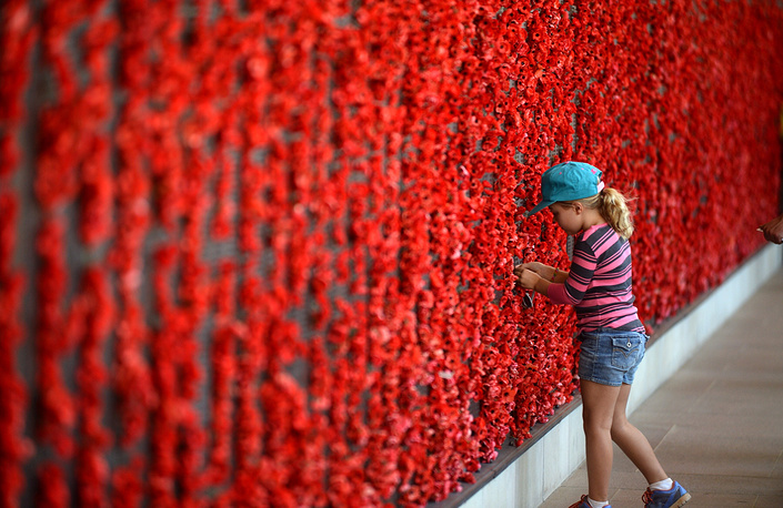 Photo: A young girl places a poppy next to a relatives name at the Australian War Memorial during the national Remembrance Day ceremony in Canberra, Australia, 11 November 2014