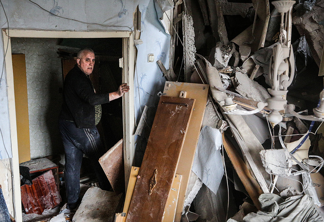 The number of internally displaced people is more than 460 thousand. Photo: Man at a badly damaged apartment building in Donetsk region
