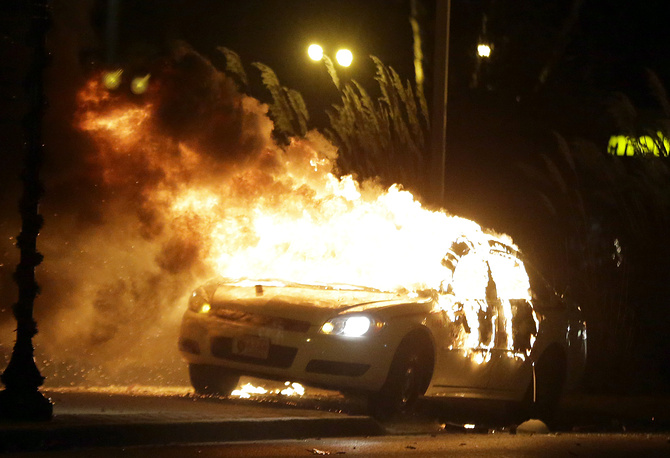 Photo: A police car is set on fire after a group of protesters vandalize the vehicle after the announcement of the grand jury decision in Ferguson