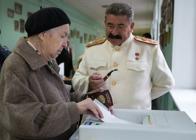 An impersonator of Josef Stalin monitors elections to the Moscow legislature at a polling station