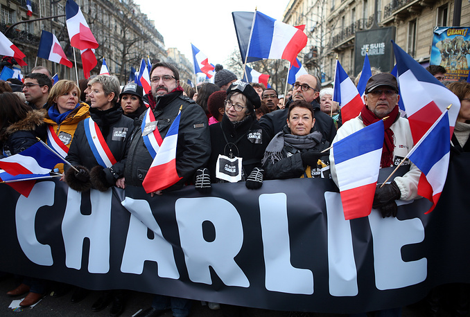 Photo: People hold a large banner that reads 'Charlie' and wave the national flag during a mass demonstration in solidarity with the victims of the terrorist attacks and to show unity, in Paris, France, 11 January 2015