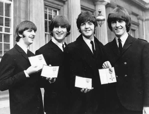 Ringo Starr, John Lennon, Paul McCartney and George Harrison display the Member of The Order of The British Empire medals presented to them by Queen Elizabeth II in a ceremony in Buckingham Palace in London, England, 1965