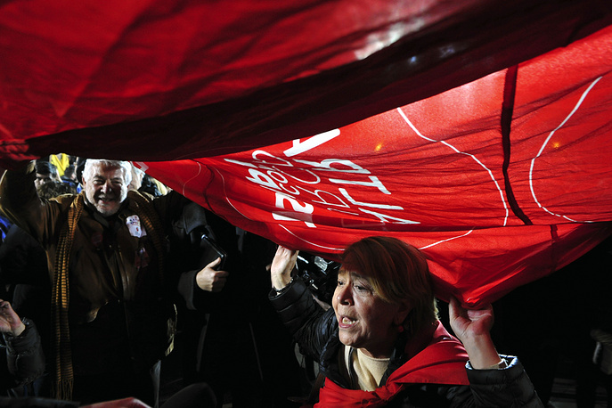 Photo: Supporters of Syriza left-wing party wave a giant flag outside Athens University Headquarters, Jan. 25, 2015