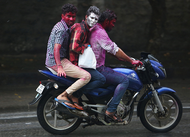 Indian men riding a motorbike on Holi festival in Hyderabad, India